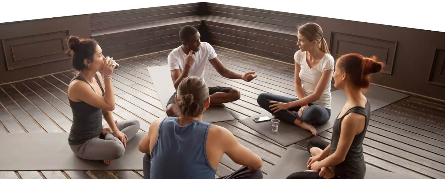 Photo of a group of people sitting in a wellness yoga class.